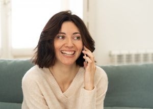 Lifestyle portrait of relaxed attractive woman talking on phone with friends smiling happy on the couch at home. In leisure internet, smartphone and social network concept.